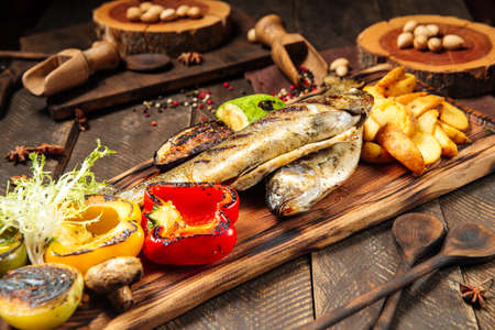 Side view on grilled fish with vegetables on the wooden board Фото со стока