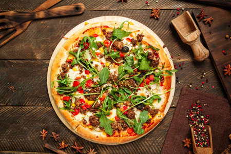Top view on pizza with minced meat and arugula on the wooden table