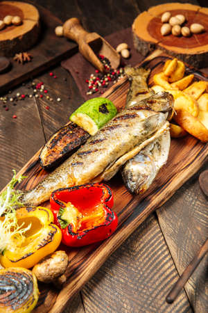 Side view on grilled fish with vegetables on the wooden board Фото со стока - 155841048