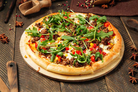 Side view on pizza with minced meat and arugula on the wooden table