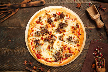 Top view on pizza with beef meat under the cheese on the wooden table Фото со стока - 155841132