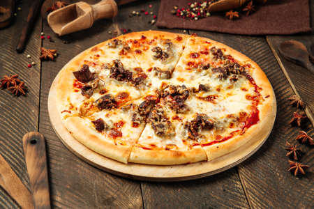 Side view on pizza with beef meat under the cheese on the wooden table