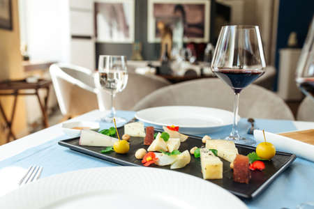 Assorted spanish cheese platter with red wine on the blue table