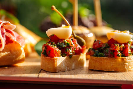 Closeup on assorted spanish tapas with different toppings on the wooden board Banque d'images