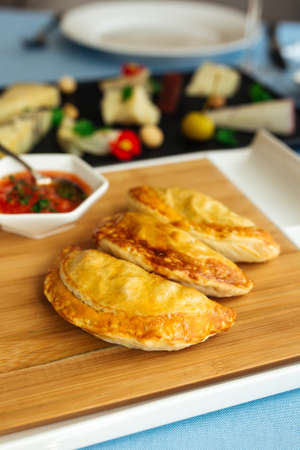 Closeup on spanish pies empanadas with sauce on the restaurant table