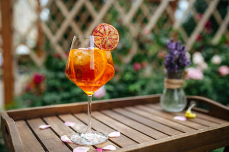 Glass of aperole spritz cocktail garnished with orange slice on the wodoen tray