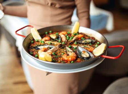 Waitress holding spanish national rice dish paella with seafood