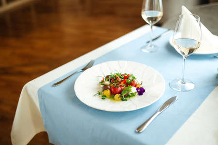 Spanish peeled tomato salad with herbs on the blue served table