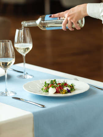 Spanish peeled tomato salad with the hand of waiter pouring white wine Фото со стока