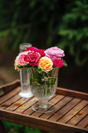 Bouquet of colorful roses in a glass vase on a leg on a wooden tray