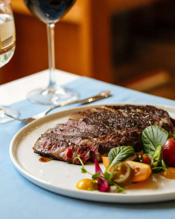 Closeup on sliced ribeye beef steak with fresh vegetable salad with red wine on the blue table