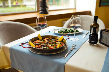 Restaurant table served with spanish dishes seafood paella and padron peppers Фото со стока