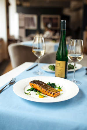 Grilled salmon fillet steak on the served blue table Фото со стока
