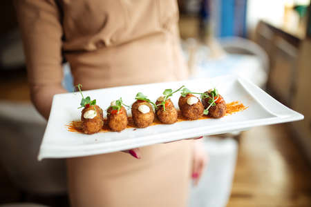 Waitress holding spanish delicacy fried potato balls croquettes