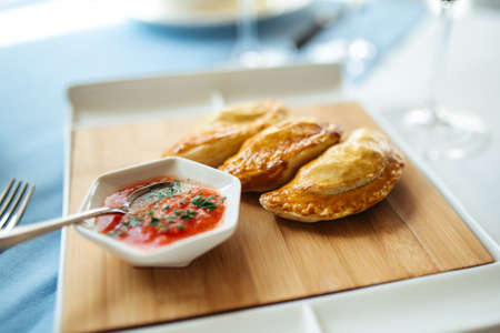Side view on spanish pies empanadas with sauce on the restaurant table
