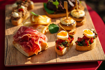 Closeup on assorted spanish tapas with different toppings on the wooden board