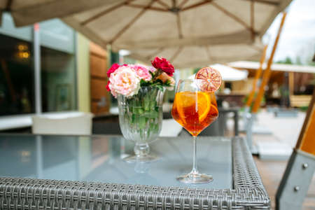 Glass of aperole spritz cocktail garnished with orange slice on the table with flowers