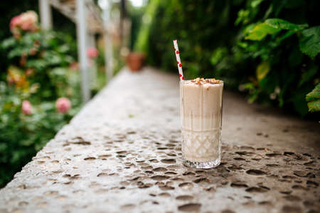 Side view on chocolate milkshake with a straw on the stone background Фото со стока
