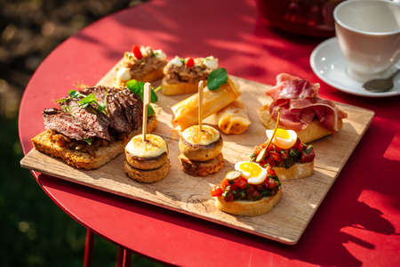Assorted spanish tapas with different toppings on the wooden board Фото со стока