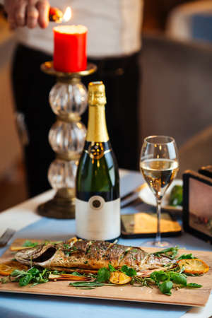 Roasted sea bass with herbs on the served restaurant table