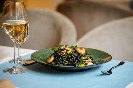 Black spaghetti with seafood and saffron sauce with white wine on the blue table