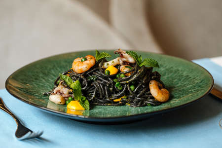 Black spaghetti with seafood and saffron sauce on the blue table