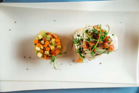 Top view on spanish dish basque baked sea bream with vegetable tartare