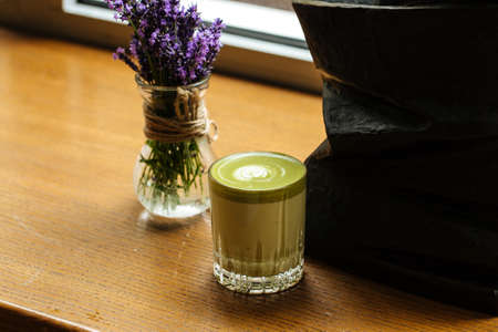 Closeup on green matcha beverage in a glass on the wooden table