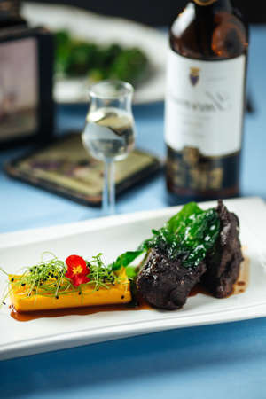 Spanish veal cheeks in wine sauce and sweet potato puree with wine bottle on the background