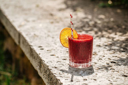 Red berry smoothie in a glass with a straw on a stone background