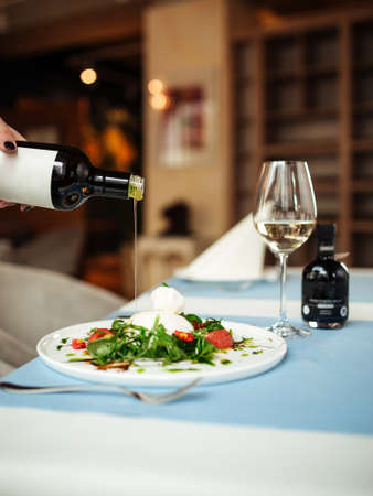 Pouring oil on spanish buratta salad on the restaurant table