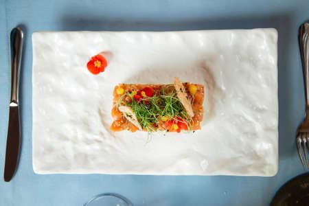 Top view on spanish salmon tartare on avocado pillow on a white plate