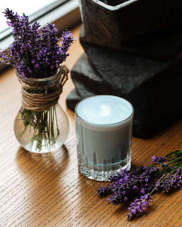 Blue lavander latte beverage in a glass on the table with flowers Фото со стока - 156370885