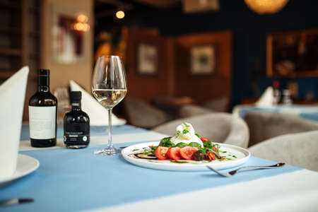 Restaurant table served with gourmet spanish buratta salad with vegetables and greens Фото со стока