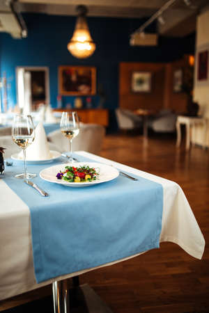 Restaurant table served with spanish peeled tomato salad with blurry background