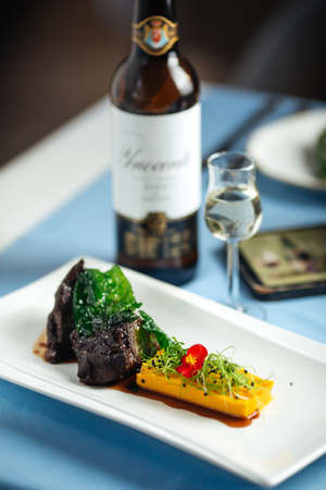 Spanish veal cheeks in wine sauce and sweet potato puree with wine bottle