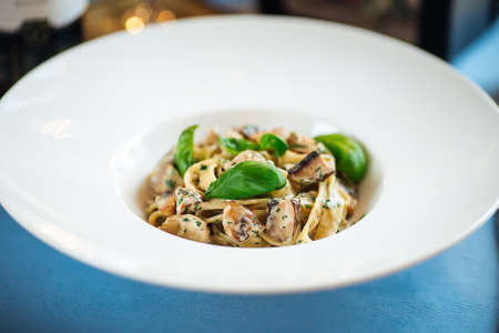 Closeup on gourmet tagliatelle with wild mushrooms in a white plate Фото со стока