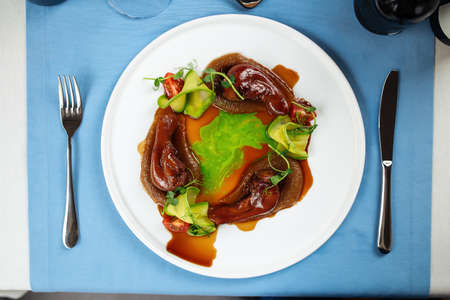 Top view on spanish dish lamb tongues with caramelized onion puree
