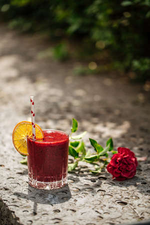 Red berry smoothie in a glass with a straw on a stone background with flower