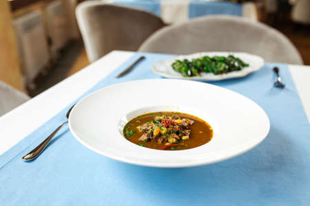 Spanish traditional oxtail soup in white plate on the blue table Фото со стока