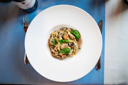 Top view on gourmet tagliatelle with wild mushrooms in a white plate Фото со стока - 156370890