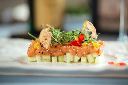Closeup on spanish salmon tartare on avocado pillow on a white plate Фото со стока - 156337223