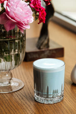 Blue lavander latte beverage in a glass on the table with flowers