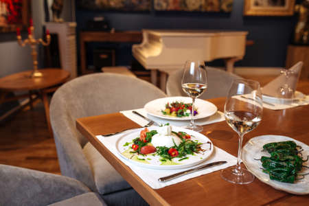 Restaurant table served with spanish buratta tomato and peppers salads Фото со стока