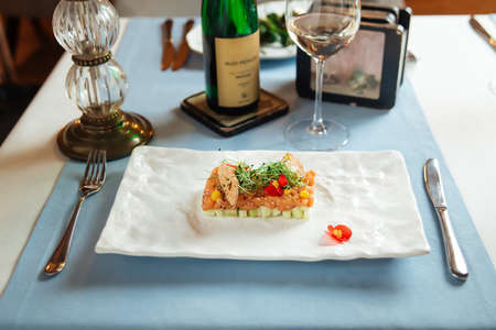 Side view on spanish salmon tartare on avocado pillow on a white plate