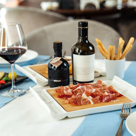 Spanish sliced pork jamon with red wine on the restaurant table Фото со стока - 156337161