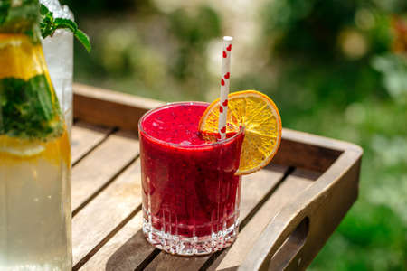Red berry smoothie in a glass with a straw on a wooden tray Фото со стока
