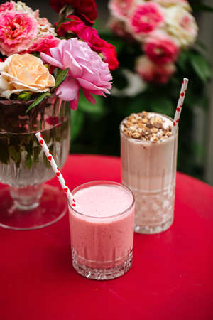 Side view on chocolate and strawberry milkshakes on the red table