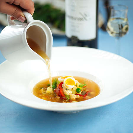 Pouring broth in a plate with soup vegetables from jug