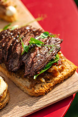 Closeup on spanish tapas with roasted beef on a toast with herbs Фото со стока - 156429482